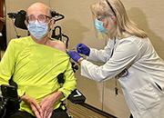 A male Veteran receives a COVID-19 vaccination